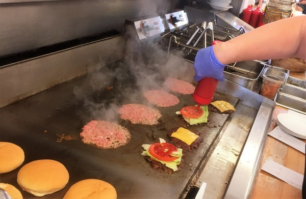 hamburgers on the grill at Carl's Drive In